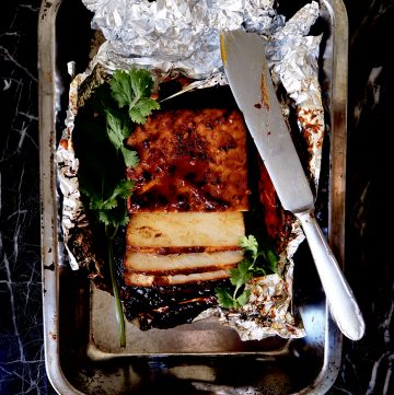 top view of sliced marinated tofu in tin foil with coriander and a sharp knife