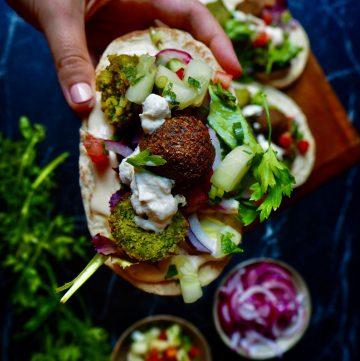 een pita met falafel en toppings vastgehouden door een hand gezien vanaf boven. op de achtergrond zijn meer pita's te zien op een houten serveerplank. tegen een donkere achtergrond.