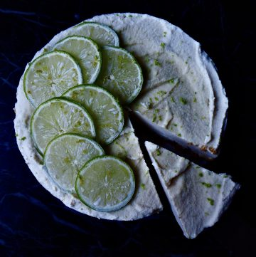 no bake lime cheesecake seen from above with a slice cut from the lower side against a dark backdrop