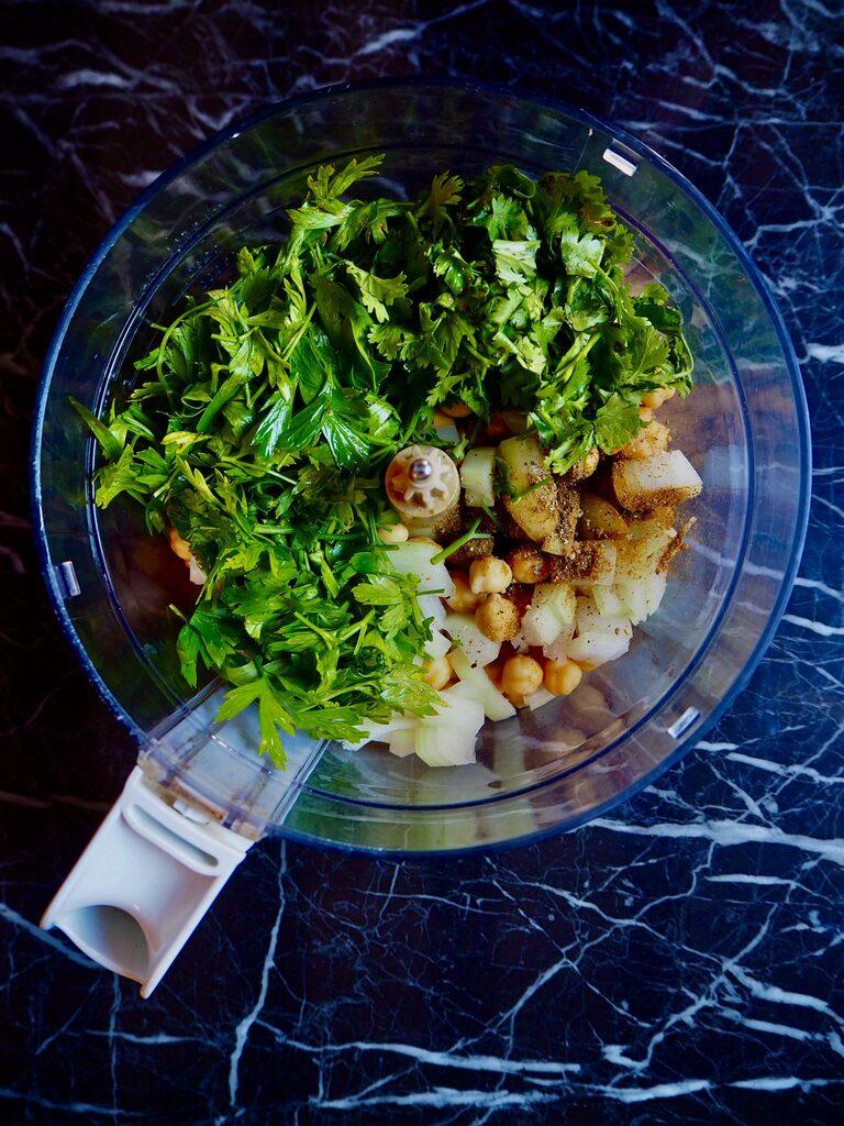 de keukenmachine met de geweekte kikkererwten, ui, verse koriander en peterselie tegen een donkere achtergrond.