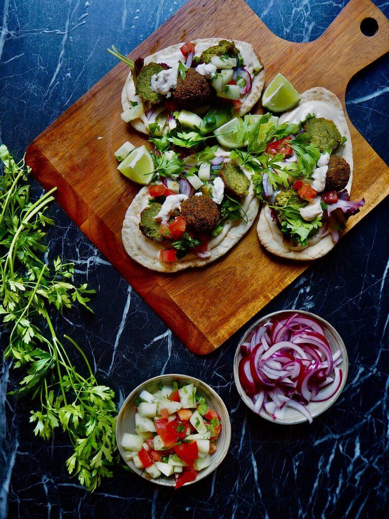 een houten serveerplank met drie pita's met falafel en toppings. linksonder een handvol verse peterselie, een klein bakje komkommer en tomaat, een klein bakje rode ui tegen een donkere achtergrond.