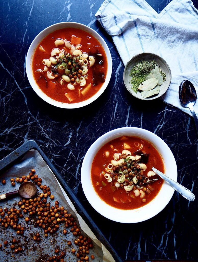from bottom to top: an oven tray with chickpeas, two bowls of minestrone, a small bowl of herbs, a spoon, and a tea towel against a dark backdrop
