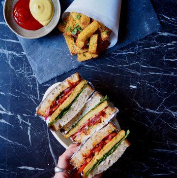 la polenta crujiente estilo patatas fritas y los sandwiches con filete de polenta vistos desde arriba con una mano izquierdo tomando uno de los sandwiches