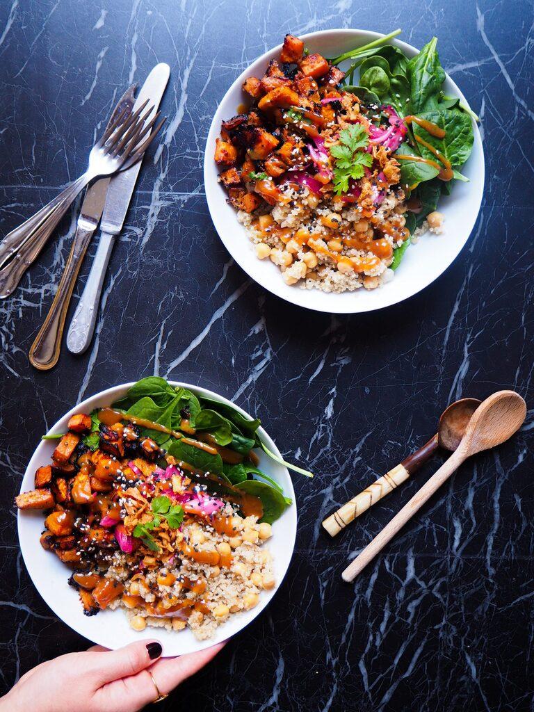 twee miso zoete aardappel en quinoa bowls gezien van bovenaf met zilver bestek en twee houten lepels tegen een donkere achtergrond