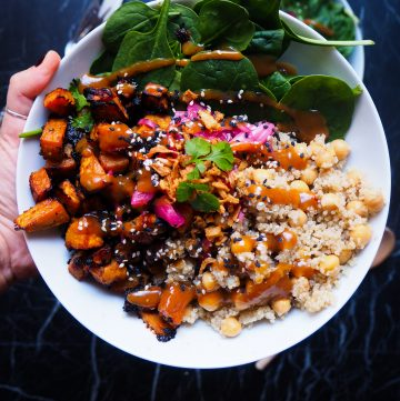 bowl with miso glazed sweet potato, quinoa, spinach, chickpeas, miso vinaigrette, red onion, and crispy onion on top seen from up close