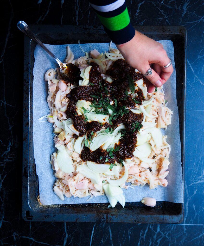 de jackfruit op een ovenschaal met ui en knoflook en de bbq saus met een linkerhand die verse salie strooit