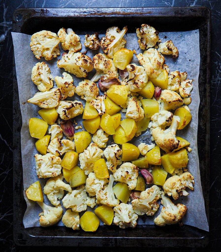 roasted cauliflower and potato and garlic in oven tray seen from above