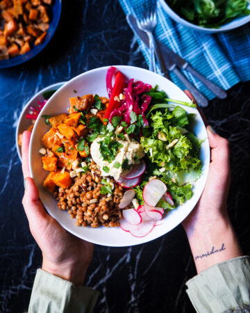 a spiced lentil and sweet potato bowl held by two hands seen up close